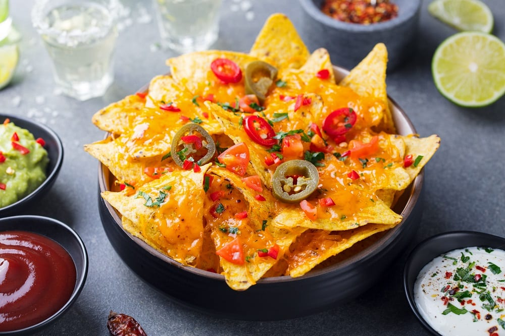 Nachos chips with melted cheese and dips variety.